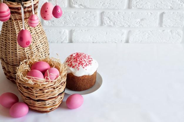 Пасхальная композиция с украшенными ветвями деревьев в плетеной вазе, розовыми яйцами в плетеной корзине и куличом на белом фоне. копировать пространство
