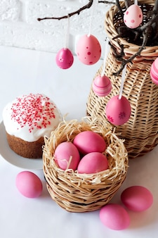 Easter composition with decorated tree branches in a wicker vase, pink colored eggs in wicker basket and easter cake on white background