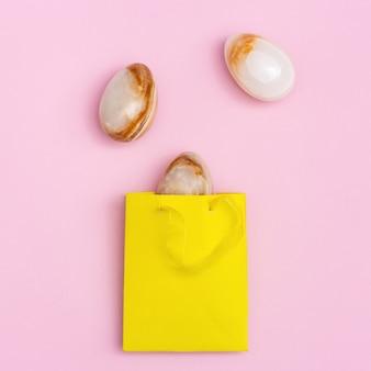 黄色い紙のパッケージの中に宝石用原石のオニキスからの装飾的な卵とイースターの構成
