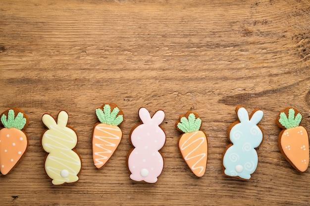 Состав пасхи с пасхальными кроликами и пряниками морковного печенья на деревянном столе. плоская планировка, вид сверху.