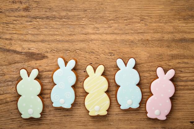Состав пасхи с пряниками печенья пасхальных кроликов на деревянном столе. плоская планировка, вид сверху.