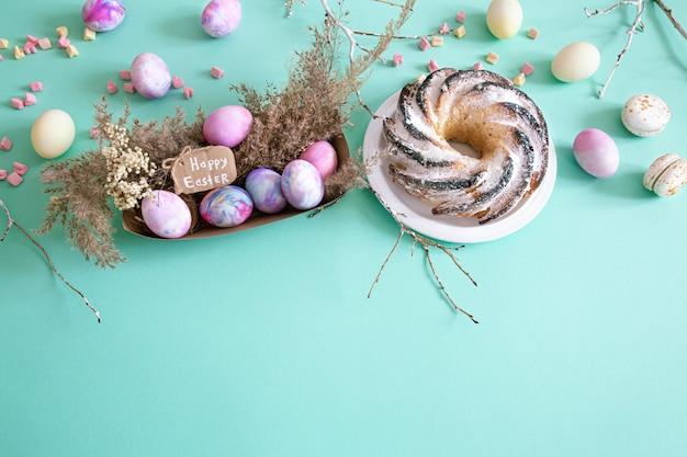 Пасхальная композиция с яйцами и кекс на цветном фоне.