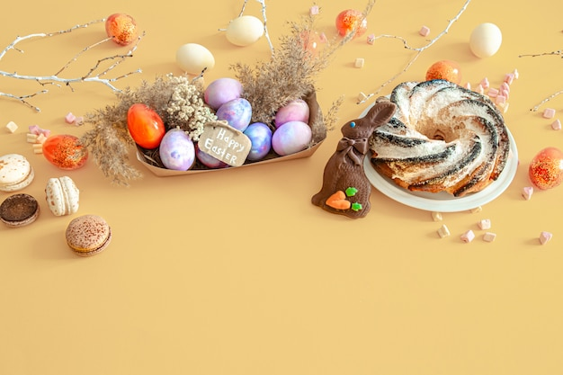 Easter composition with eggs and cupcake on colored.