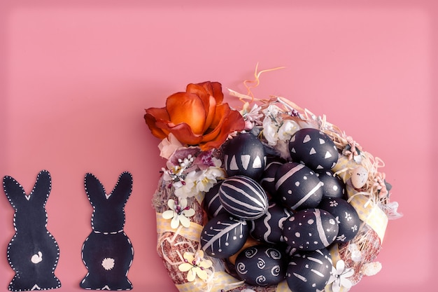 Easter composition with eggs and the easter bunny on a pink table