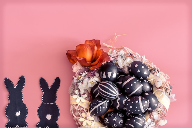 Easter composition with eggs and the easter bunny on a pink wall