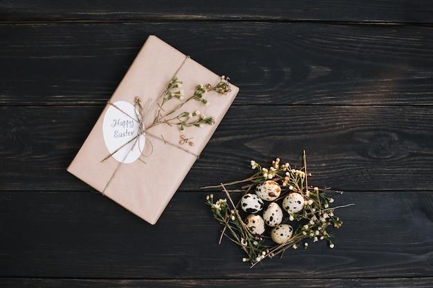 Пасхальная композиция с яйцами, подарком в крафт-бумаге и сухими ветками на темной деревянной поверхности