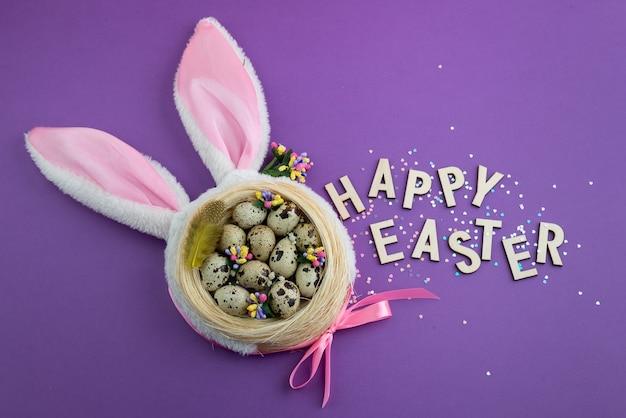 紫色の表面の巣に卵を入れたイースターの構成