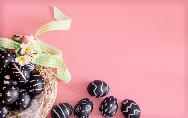 Easter composition with eggs on a pink table