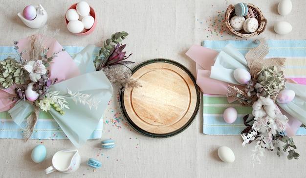Пасхальная композиция с цветами, яйцами и деревянным пространством для текста в пастельных тонах.