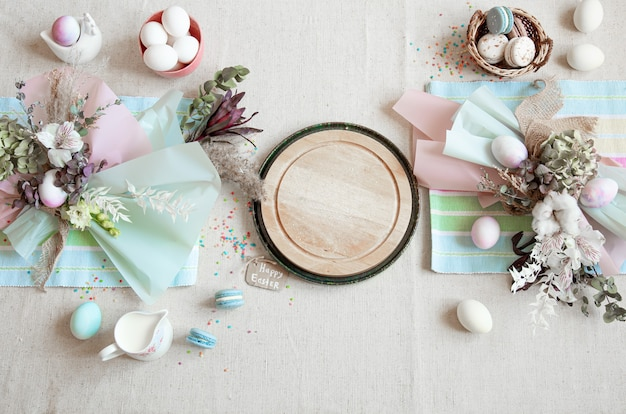 Easter composition with flowers, eggs and wooden space for text in pastel colors flat lay.