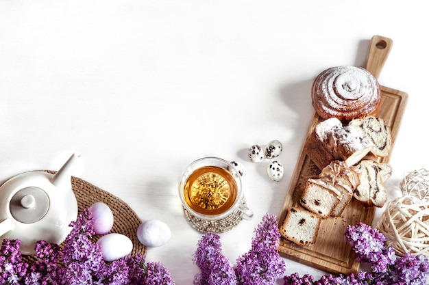 신선한 파이, 차 한 잔, 신선한 라일락 꽃과 부활절 구성. 휴일 티 파티 개념.
