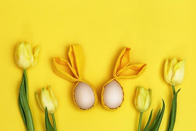 ウサギの耳と新鮮な黄色い花のチューリップの花束と手作りのカラフルなイースターエッグのイースター構成