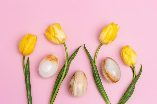 チューリップの自然の花と宝石用原石のオニキスからの装飾的な卵とイースターの構成