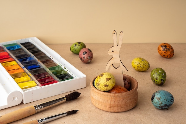 バスケットに描かれた卵、ウサギ、工芸品の背景にペイントされたイースターの構成。イースターの伝統、背景。イースターのお祝いの準備、創造的なコンセプト。