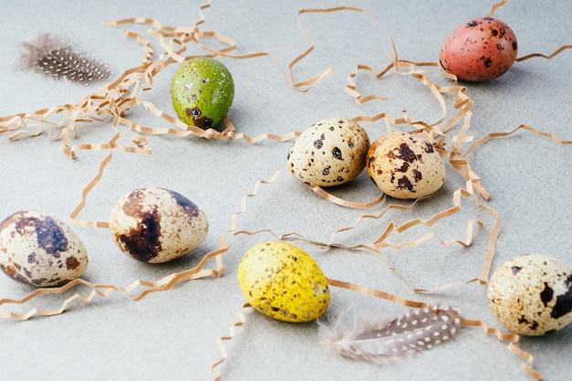 灰色の背景、コピースペースの巣に描かれた卵とイースターの構成。イースターの伝統、背景。イースターのお祝いの準備、創造的なコンセプト。