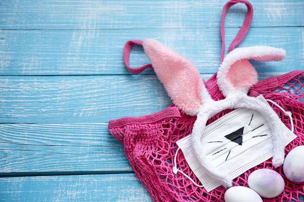 ピンクのストリングバッグ、装飾的なイースターバニーの耳、医療用マスク、木製の表面に卵が付いたイースターの構成