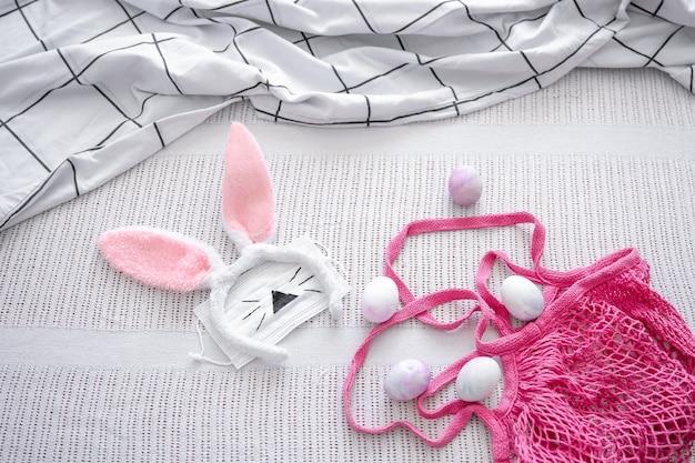 Composizione pasquale con un sacchetto di corda rosa, orecchie da coniglio pasquali decorative, una maschera medica e uova