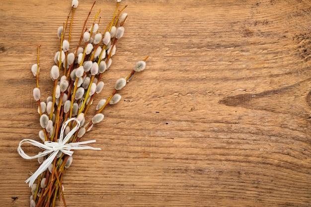 나무 테이블에 갯버들 가지와 부활절 구성. 평면 평신도, 평면도.