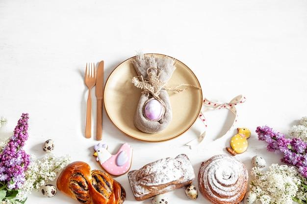 Пасхальная композиция с настройкой, выпечкой и сиреневыми цветами на столе.