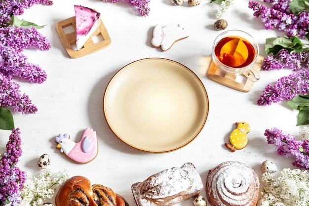 Пасхальная композиция с сервировкой, чаем, выпечкой, деталями декора и цветами сирени на столе. пасхальный обед за праздничным столом.
