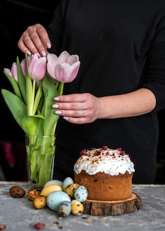 Easter composition with sweet bread, kulich and eggs on a gray surface