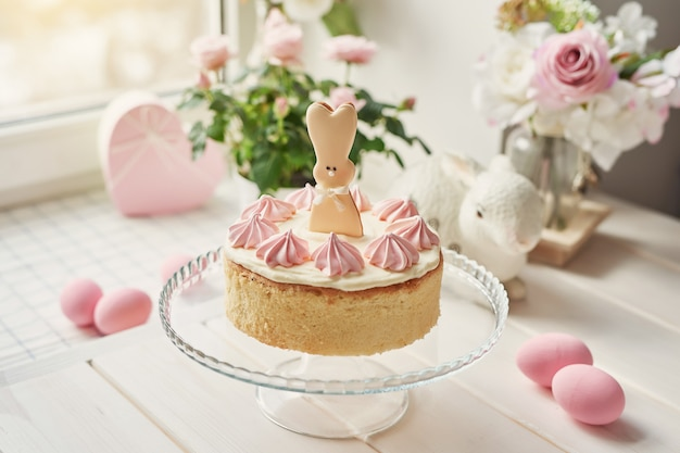 Easter composition with sweet cake with strawberry icing, ceramic bunnies, pink eggs and roses