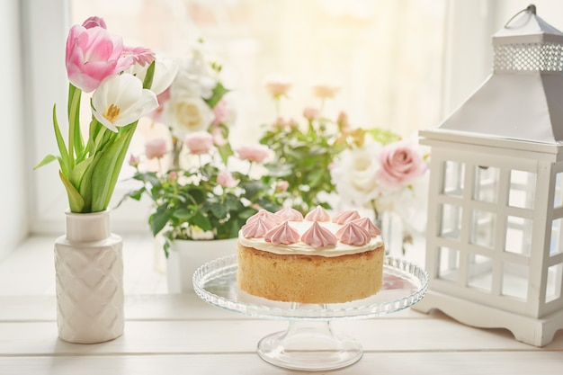 Easter composition with sweet cake with strawberry icing and roses