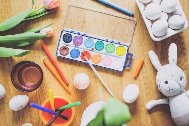 부활절 달걀과 나무 테이블에 꽃 그림 도구로 구성. 위에서 봅니다.