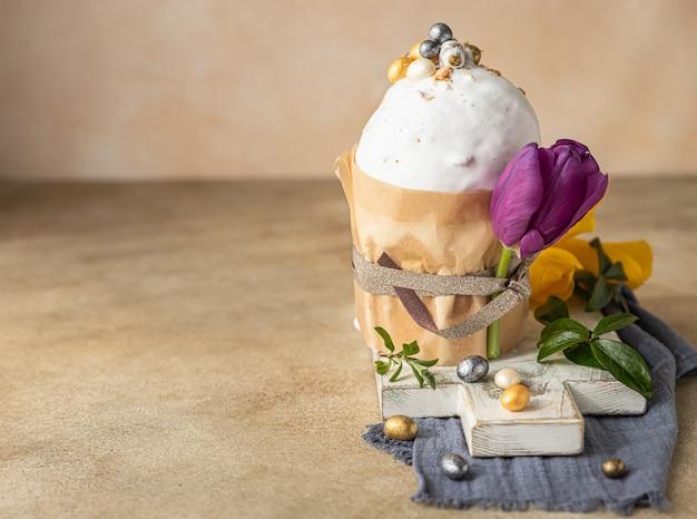 Пасхальная композиция с традиционным православным сладким хлебом кулич, украшенным глазурью из безе