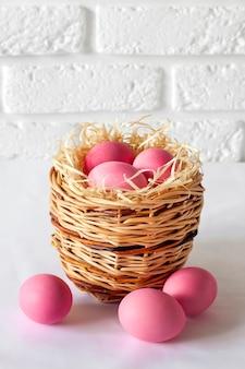 枝編み細工品バスケットとピンク色の卵のイースター組成
