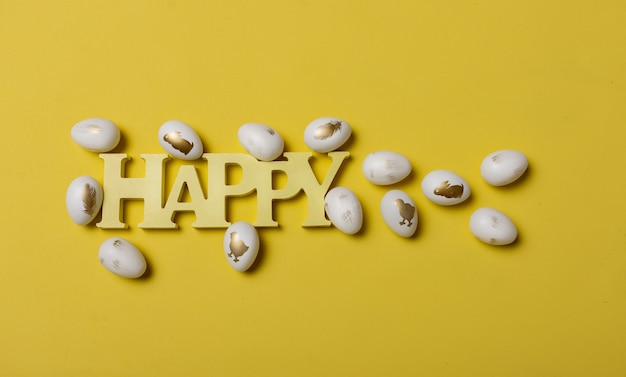 幸せな木製の単語とテキストの場所と黄色の背景に卵とイースターの構成