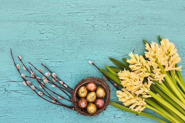 Пасхальная композиция с желтыми гиацинтами, вербой и пасхальными яйцами. вид сверху, копия пространства.