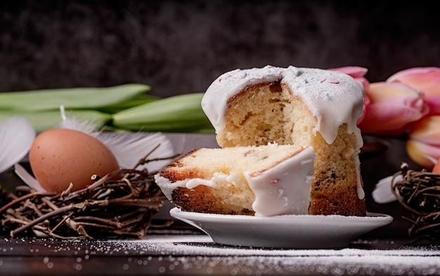 Концепция пасхи. выпечка и приготовление пищи. глазированный пасхальный кулич с тюльпанами на темном деревенском фоне