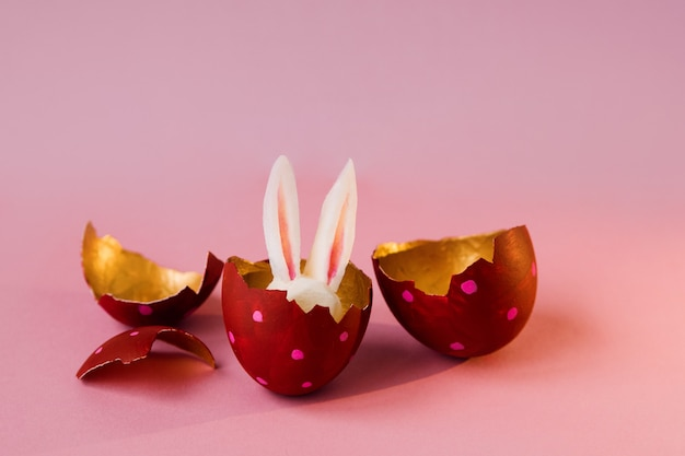 Easter concept. colored eggs on pink background, easter bunny hiding
