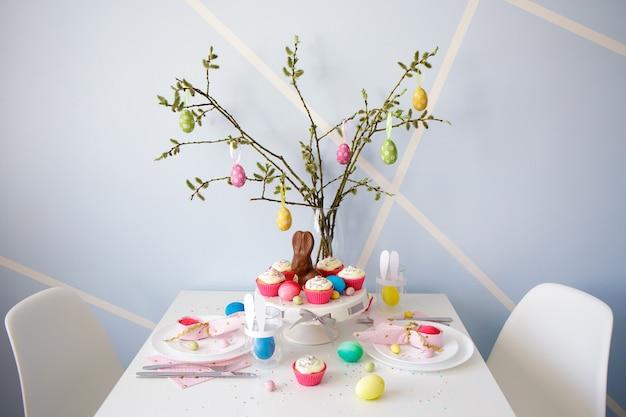 Концепция пасхи - украшенный стол с кексами, разноцветными крашеными яйцами и кроликами