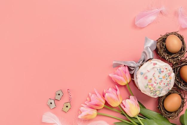 Концепция пасхи. пасхальный кулич с тюльпанами и яйцами на розовом фоне, плоский вид сверху с копией пространства
