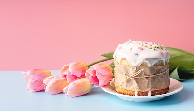 イースターのコンセプト。コピースペースとピンクと青の背景正面図にチューリップとイースターケーキ