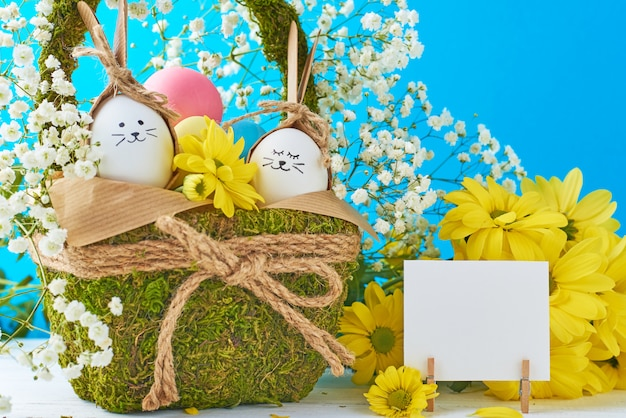 Easter concept. eggs in basket decorated with flowers on a blue background