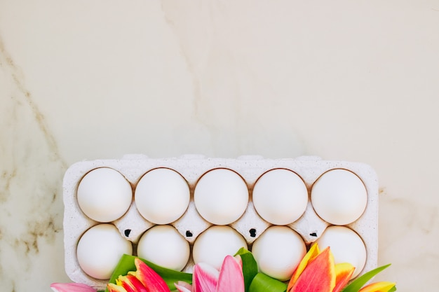 Easter concept, flat lay chicken eggs and colorful tulips on marble background. top view.