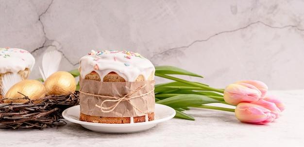 Концепция пасхи. глазированный кулич с тюльпанами и крашеными яйцами, вид спереди