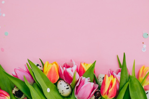 Easter concept, golden star decorations, vibrant confetti and multicolored tulips and quail eggs on pink background.