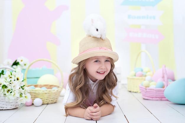 부활절 개념! 웃는 소녀는 그녀의 머리에 부활절 토끼를 보유하고있다. 부활절 장식. 농업. 어린이와 정원. 작은 농부. 아이는 솜털 토끼를 가지고 놀아요. 어린이와 동물. 봄 꽃