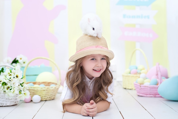 Easter concept! little smiling girl holds an easter bunny on her head. easter decor. agriculture. child and garden. little farmer. a child plays with a fluffy rabbit. child and animal. spring flowers