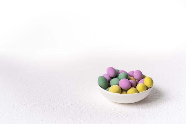 Концепция пасхи. мини-яйца в маленькой тарелке на белом фоне. цветной узор яиц, пасхальный фон.