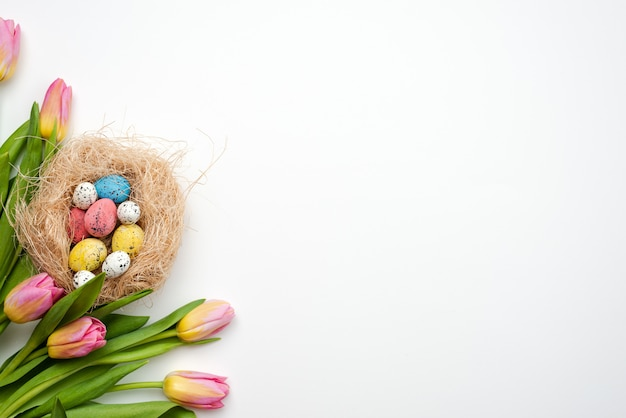 Easter concept, multi-colored eggs and bouquet of tulips lie on a white table. - copy space