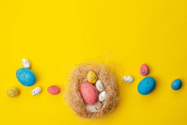Easter concept, multi-colored eggs in a nest lie on a yellow table. - copyspace