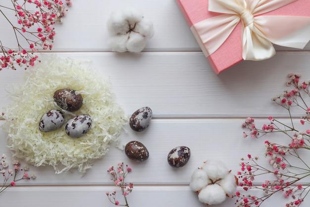 イースターのコンセプト自然に染められた卵と綿の花の装飾と木製のテーブルのギフトボックス