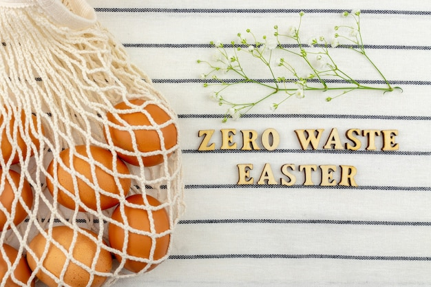 イースターのコンセプト。ビニール袋のコンセプトはありません。最小限のスタイル。テキスタイルの背景に茶色の鶏の卵とベージュのメッシュのショッピングバッグ。