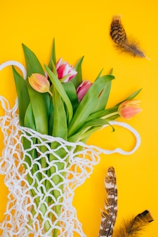 Easter concept. spring bouquet of multicolored tulips in eco bag with and quail eggs and feathers on a yellow background. copy space, flat lay background.