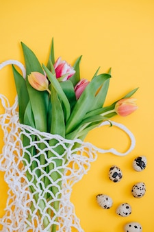 Easter concept. spring bouquet of multicolored tulips in eco bag with and quail eggs on a yellow background. copy space, flat lay background.